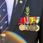 Image of ANZAC returned serviceman wearing rosemary with his medals.